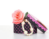 Pearls inside open gift box with pink rose on white background — Stock Photo
