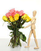 Wooden puppet with bounqt pink rose — Stock Photo