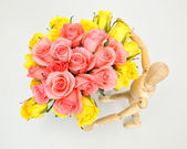 Wooden puppet with bouquet pink rose view top — Stock Photo