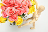 Close up wooden puppet with bouquet pink rose view top — Stock Photo