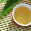 Foto Stock: Teapot,tecup and pandam leaves on bamboo mat