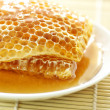Foto Stock: Close up sweet honeycombs on bamboo mat