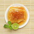 Foto Stock: Sweet honeycombs in dish with lemon and mint on bamboo mat