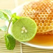 Foto de Stock  : Close up half lemon with sweet honeycombs and mint leaf