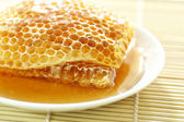 Close up sweet honeycombs on bamboo mat — Stok fotoğraf