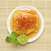 Sweet honeycombs in dish with lemon and mint on bamboo mat — Stok fotoğraf