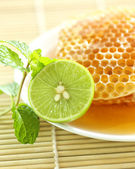 Close up half a lemon with sweet honeycombs and mint leaf — Stockfoto