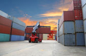 Forklift handling the container box at dockyard with harbour bac — Stock Photo