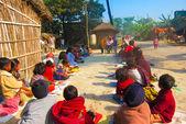 People sitting near native houses — Photo
