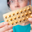 Stock Photo: Birth control pills in hands of young woman