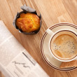 Coffee, muffin and a newspaper — Stock Photo