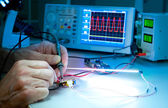 Modern oscilloscope on working bench — Stock Photo