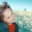 Happy little boy on a flower field — Stock Photo