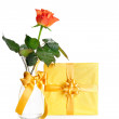 Gift box in yellow wrapping paper and a rose — Stock Photo