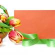 Basket of tulips and an orange envelope — Stock Photo