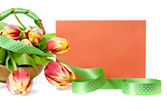 Basket of tulips and an orange envelope — Stock Photo