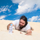 Thirsty man in the desert reaches for water — Stock Photo