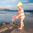 图库照片: Little boy plays with water on beach
