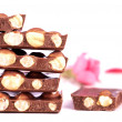 Pile of chocolate chunks with nuts and a rose — Stock Photo