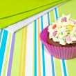 Decorated cupcake on stripy background — Stock Photo #33481541