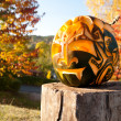 Halloween pumpkin on a wooden stump outside — Stock Photo