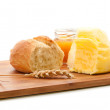 Bread roll, butter and honey on cutting board — Stock Photo