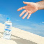 Bottle of water in the desert — Stock Photo