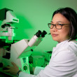 Young oriental scientist with microscope  — Stock Photo