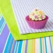 Decorated cupcake on stripy tablecloth — Stock Photo