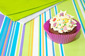 Decorated cupcake on stripy background — Stock Photo