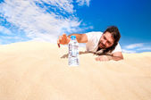 Thirsty man in the desert reaches for a bottle of water — Stock Photo