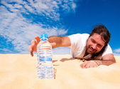 Thirsty man reaching for a bottle of water — Stock Photo