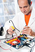 Senior tech tests electronic equipment — Stock Photo