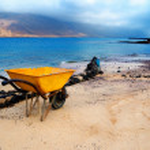 Stained yellow wheelbarrow on shore of Graciosa, Canary island — Stock Photo