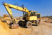 Yellow excavator on construction site — Stok fotoğraf