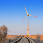 Railroad leading towards modern windmill — Stock Photo