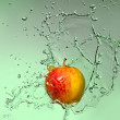 Apple with splashes of water — Stock Photo