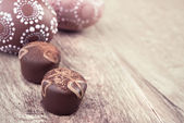 Closeup on chocolate truffles and eggs on wood — Stock Photo