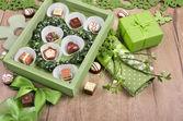 Spring arrangement with chocolate pralines — Stock Photo