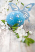 Blue Easter egg, butterfly and flowers — Stock Photo
