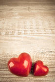 Dwa kamienne serca na drewnianym stołem — Zdjęcie stockowe
