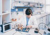 Scientist repairs electronic device — Stock Photo