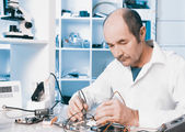 Male tech repairs circuit board — Stock Photo