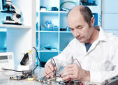 Tech repairs circuit board — Stock Photo