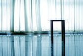 Stolik przed białe zasłony oświetlony — Zdjęcie stockowe