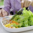 Girl eating salad with knife and fork — Stock Photo