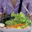 Girl with knife and fork eating salad — Stock Photo