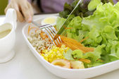 Girl eating salad with knife and fork — Foto de Stock