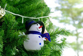 Snowman ornament on pine tree — Stock Photo