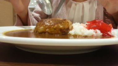 Eating Japanese food, hamburg with curry over rice. spoon and fork open up the meat — Stock Video